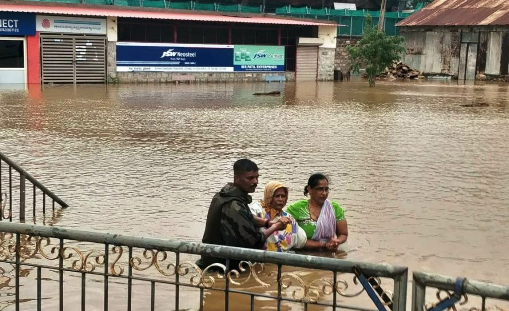 Army man assisting elderly lady in flood affected region